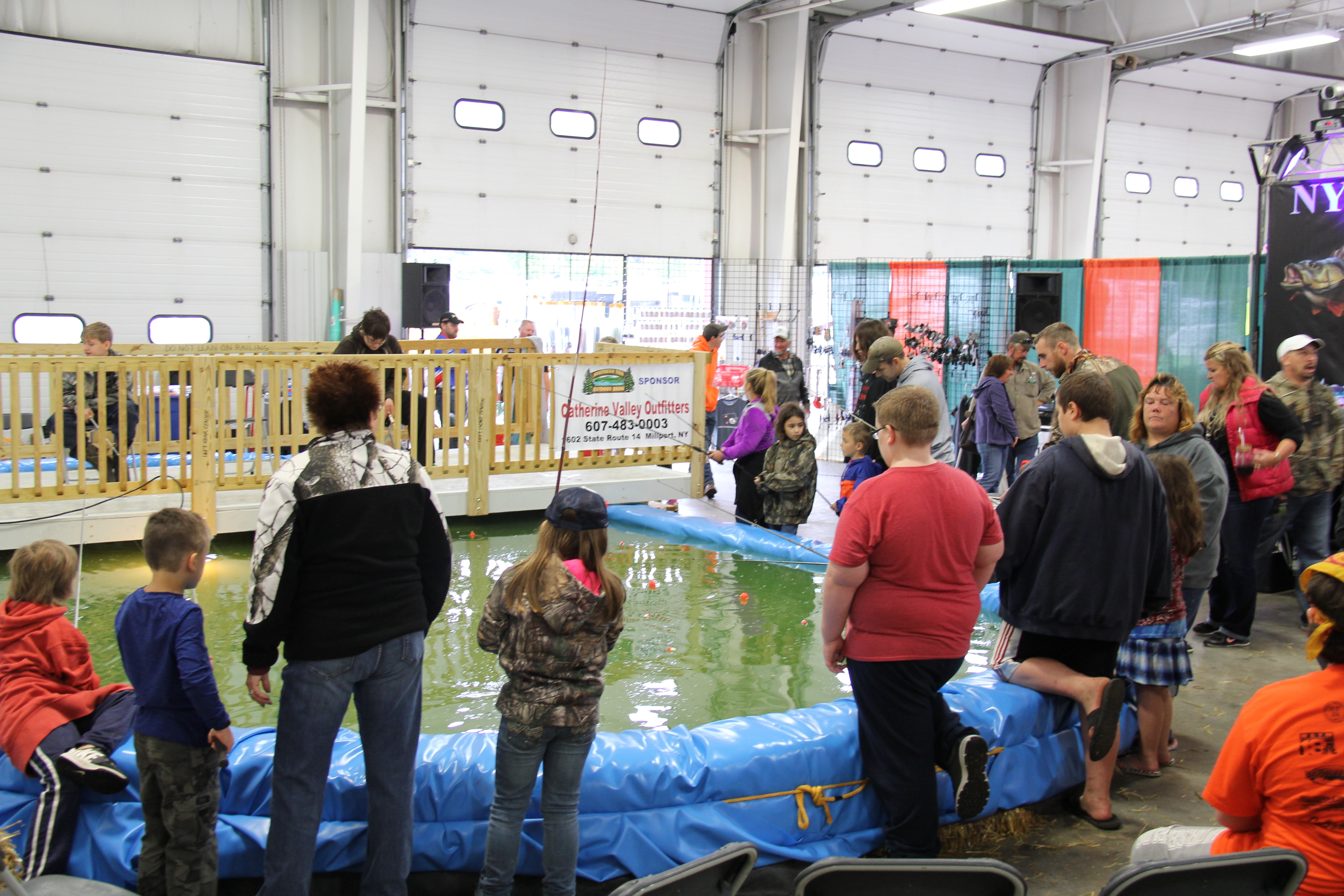 Children at an outdoor expo fishing for trout and catfish.